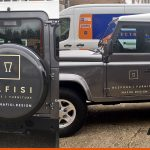Logo details on side and tyre cover of a LandRover Defender for Nafisi | Sussex Van Graphics